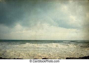 Vintage aged photo seascape wave and sea foam.