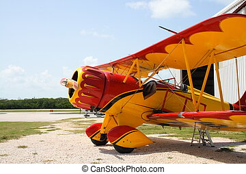 Colorful vintage airplane by a hanger