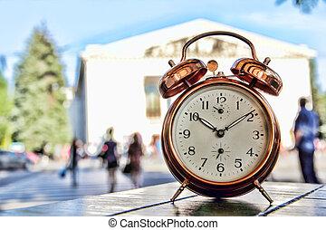 Vintage alarm clock on table against sity prospective.