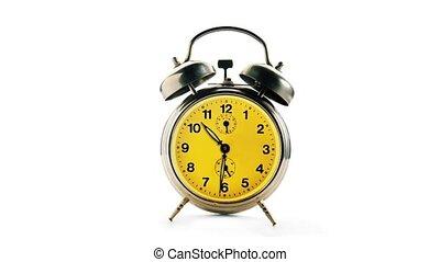 Vintage alarm clock over a white background. Time running backwards, full turn.