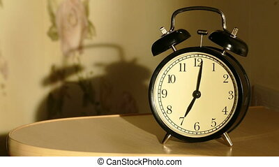 Vintage alarm clock on nightstand counts the time and then...