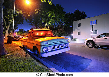 Vintage American pickup truck at night on a street in Los Angeles, California, USA.