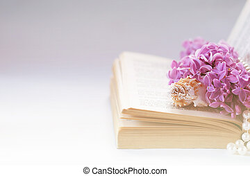 Vintage background with old book, lilac flower, and pearls. Romantic backdrop good for wedding invitation or greeting card with copy space.