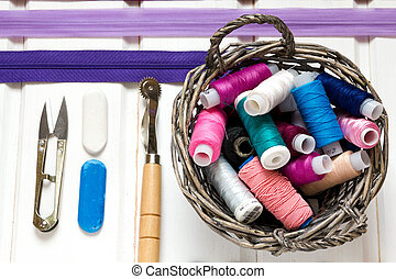 Vintage background with sewing accessories, tools, sewing kit. Scissors, bobbins with thread and needles on the old wooden white background