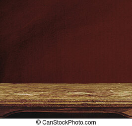 Vintage background with wooden table and grunge red wall