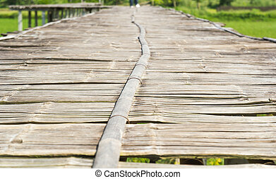 Vintage bamboo bridge on rice field.