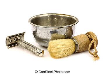 vintage barber shaving brush with metal shaving bowl and razor on a white background