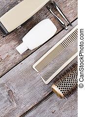 Vintage barber shop tools on rustic wooden background.