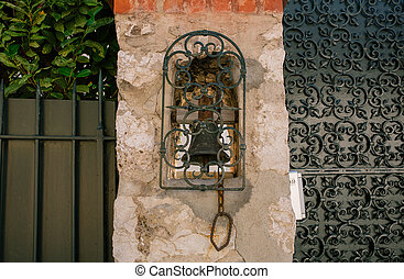 Vintage bell on the wall in the southern European city