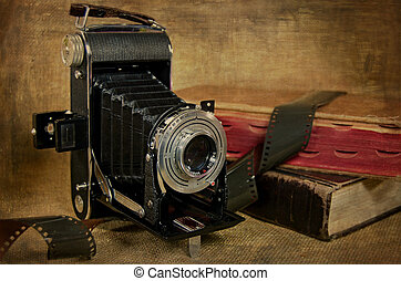 Old-fashioned bellows camera with filmstrip and books with textured overlay.
