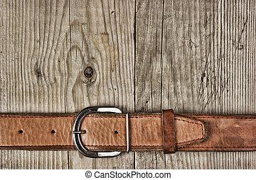 vintage belt buckle on a old wooden board
