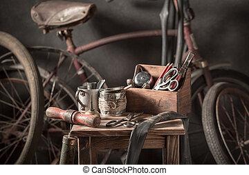 Vintage bicycle repair workshop with tools, wheels and tube