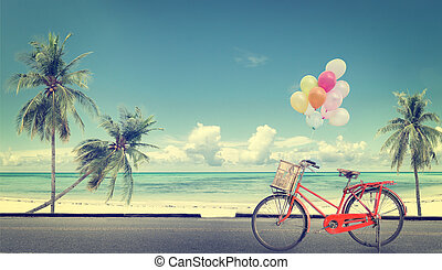 vintage bicycle with balloon on beach blue sky