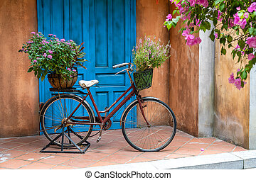 Vintage bike with basket full of flowers next to an old building in Danang, Vietnam, close up