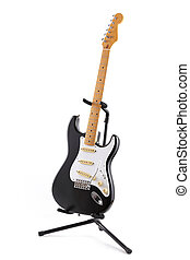Vintage black and white electric guitar on a stand isolated on white