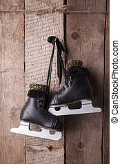 Vintage black ice skates for figure skating hanging on the background of wooden wall.