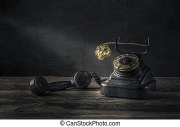 Vintage black phone on old wooden table background