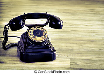 Vintage black phone on wooden table background