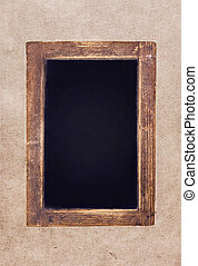 Vintage blackboard hanging on textured background. Blank Chalk board with copy