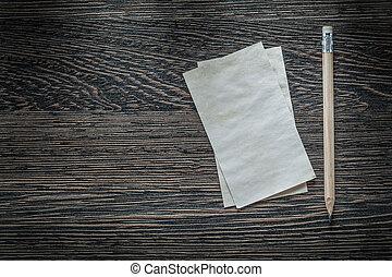 Vintage blank paper sheet pencil on black board