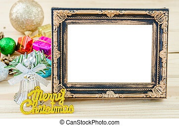 Vintage blank photo frame with christmas decorations on wood background.