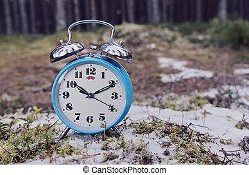 Vintage blue alarm clock on winter forest background