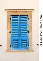 Vintage blue close window with shutters in old stone house