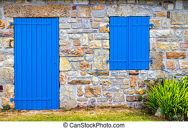 Vintage blue door and window on the facade of an old cottage stone wall.