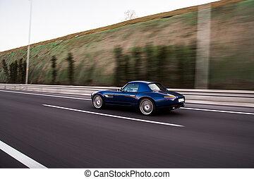 Vintage blue sedan high speed drive on the road