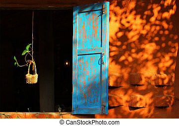 Vintage blue window frame with plant on the basket