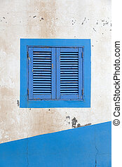 Vintage blue window shutter on the old house