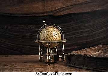 Vintage book and little globe on a wooden background