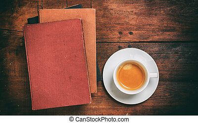 Vintage books and a cup of coffee on wooden background