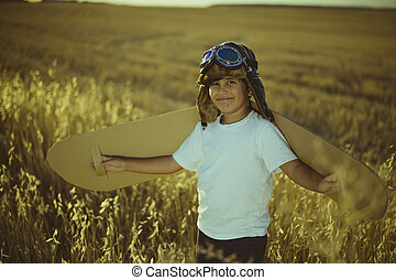 Vintage, Boy playing to be airplane pilot, funny guy with aviator cap and glasses, carries wings made of brown cardboard as an airplane