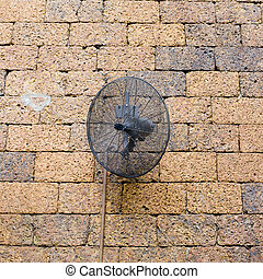 vintage brick wall with black metal fan.