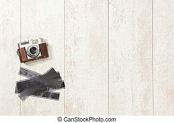 Vintage Camera And Film Strips On Floorboard