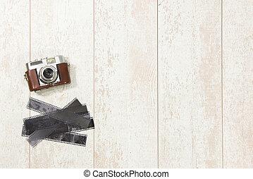 Vintage Camera And Film Strips On Floorboard
