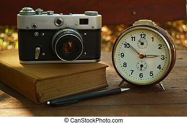 Vintage camera on book and clock