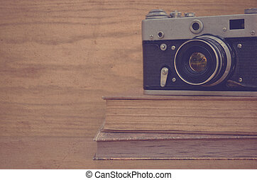 Vintage camera on book on wooden background