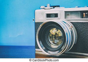 vintage camera on wooden table over blue background