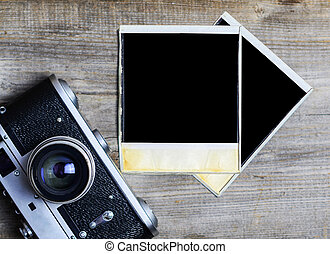 Vintage camera with blank old photograph on wooden background -