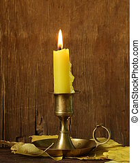 vintage candlestick with candle on the wooden background