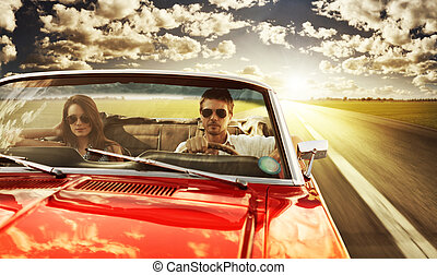 Couple taking a road trip in vintage convertible