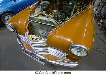 vintage car on the repair in a car workshop.