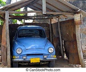 vintage car under a dilapidated carport