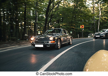 Vintage car with front lights on rushing in the forest