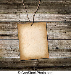 Vintage cardboard card on a rope. Wooden background