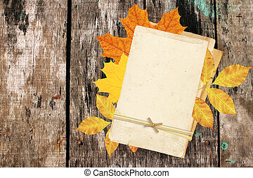 Vintage cards and autumn leaves on old wooden plank.