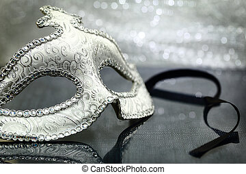 Vintage carnival mask in front of glittering background