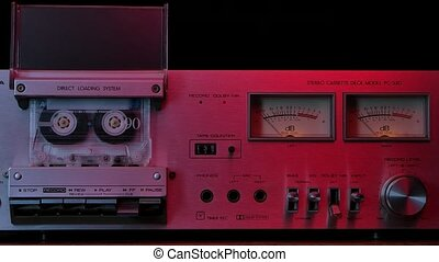Vintage cassette player deck from 80s illuminated by red neon lights. Stereo recorder with rotating cassette, controls, dashboard and buttons on black studio background. Close up. Slow motion